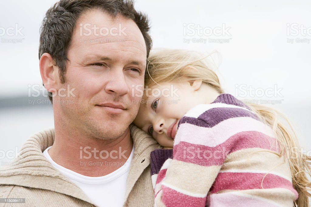 Father holding daughter at beach royalty-free stock photo