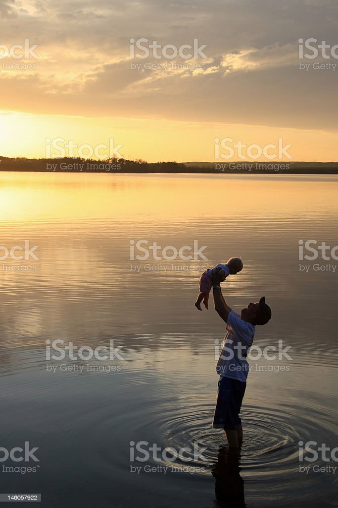 Father Holding Daughter at Sunset royalty-free stock photo