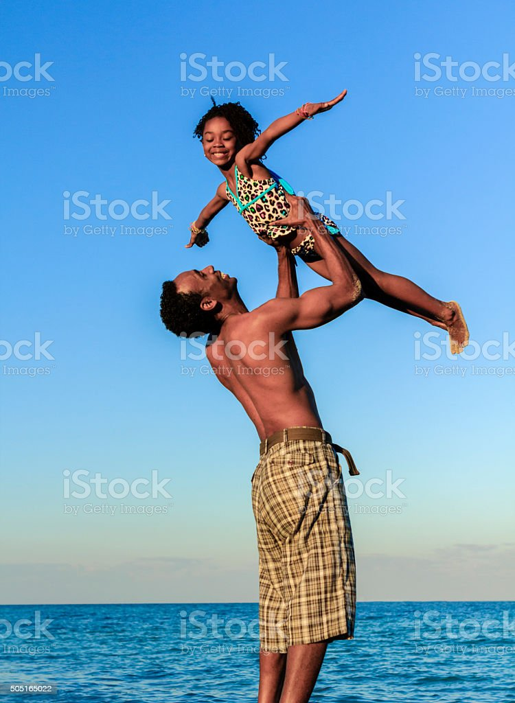 Father holding daughter in air at beach stock photo