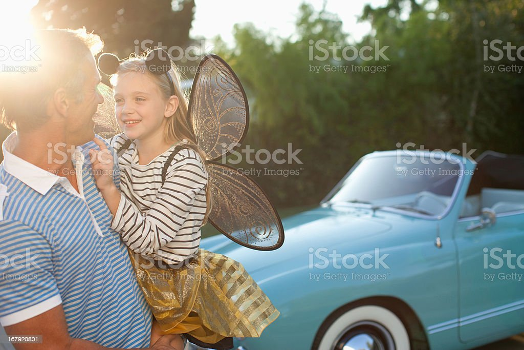 Father holding daughter in fairy wings stock photo