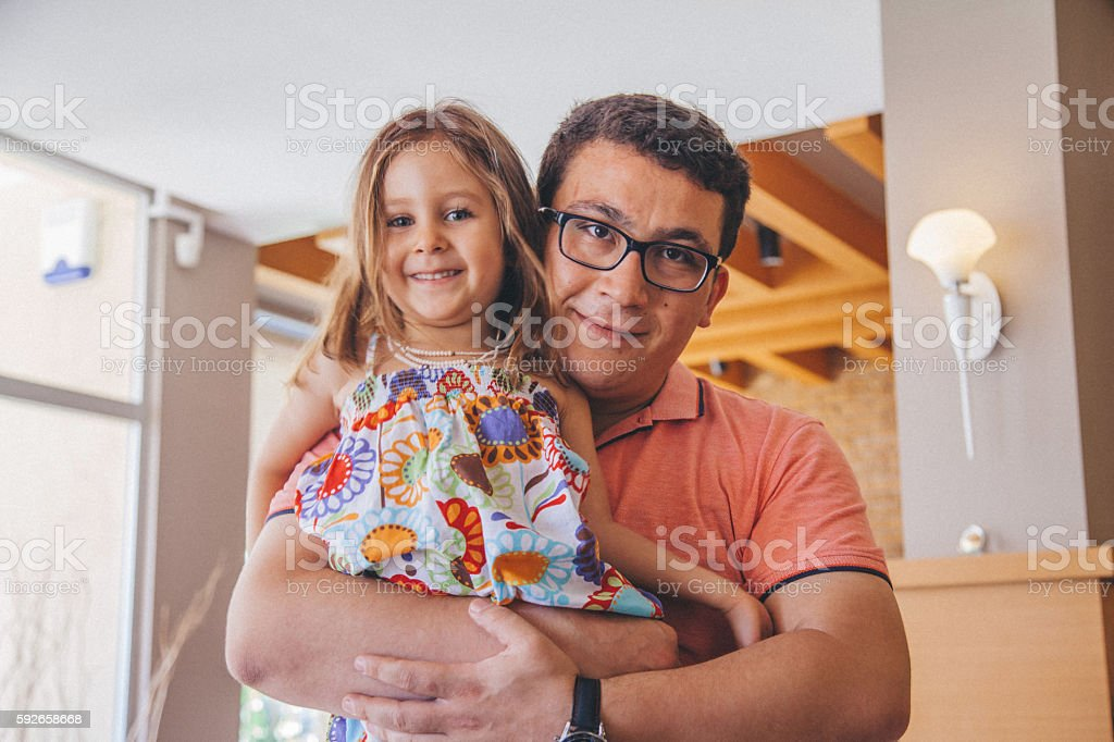 Father holding daughter posing stock photo