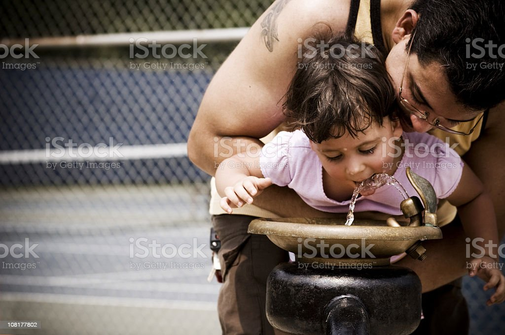 Father holding daughter up to water fountain stock photo