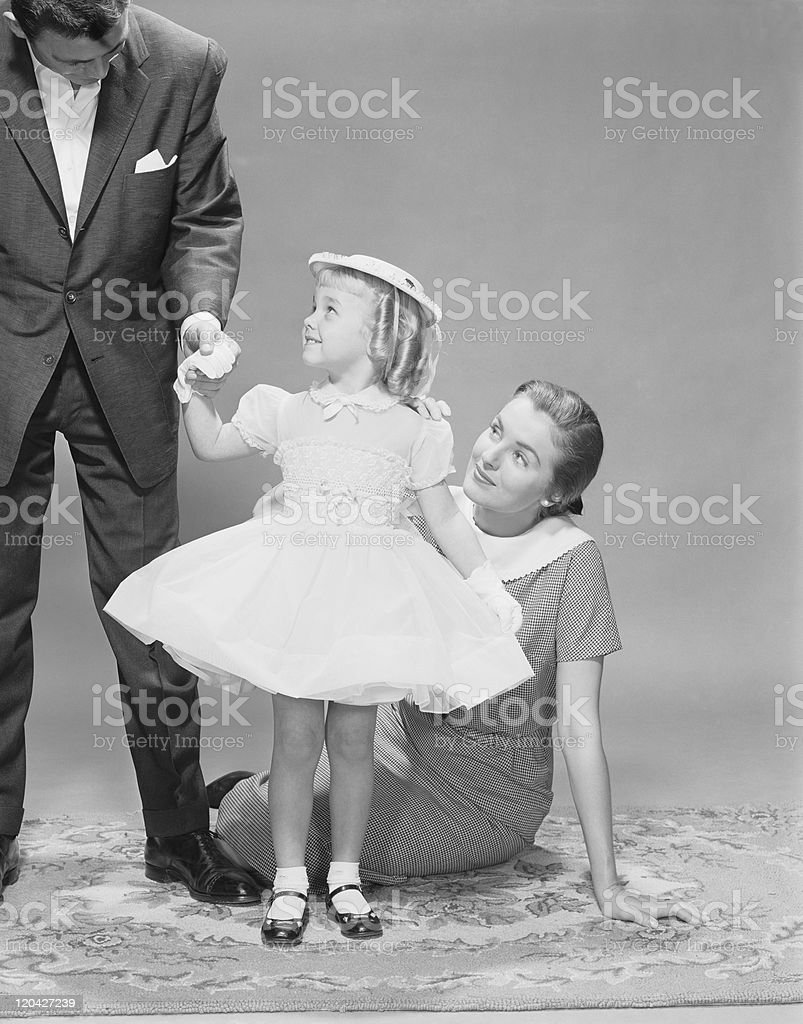 Father holding daughter's hand while mother looking at them stock photo