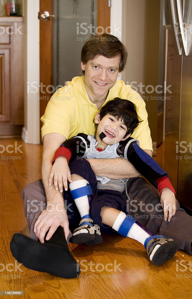 Father holding disabled son on kitchen floor stock photo