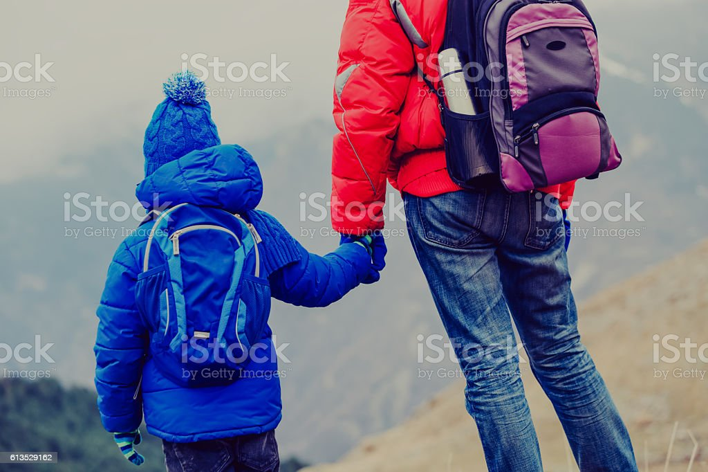 father holding hand of son while travel in mountains stock photo