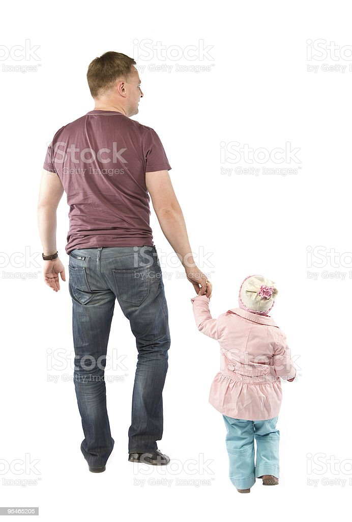 A father holding hands and walking with his young daughter royalty-free stock photo