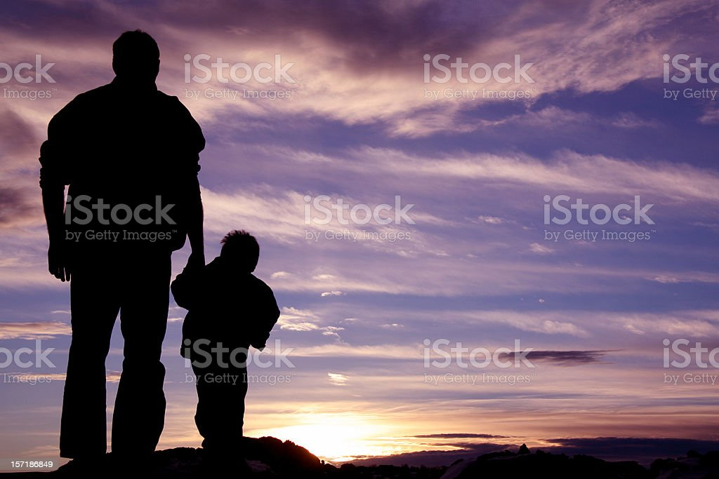 Father Holding Hands With Child Silhouette stock photo