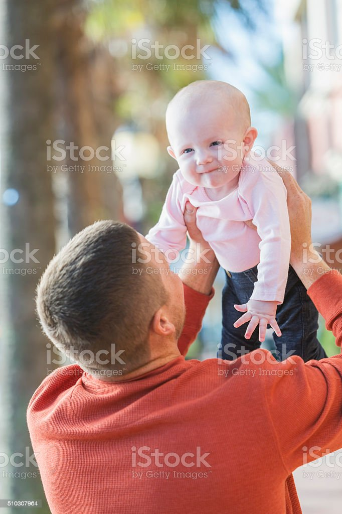 Father holding his baby girl aloft stock photo