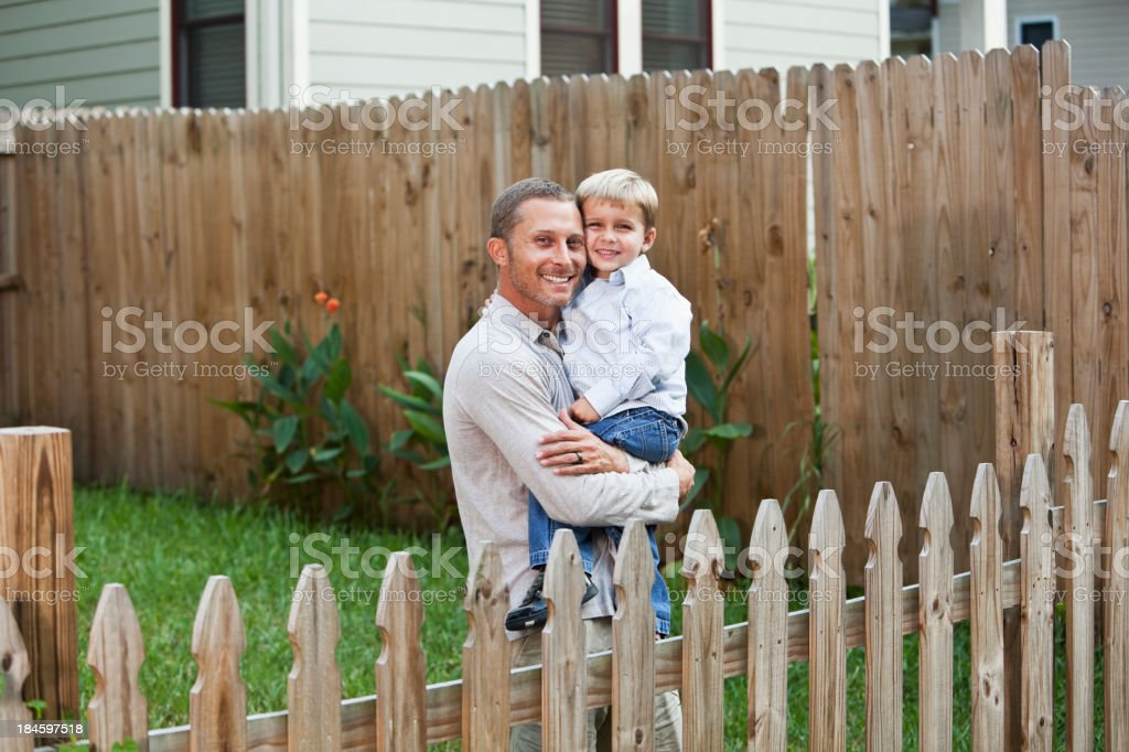 Father holding little boy in backyard stock photo