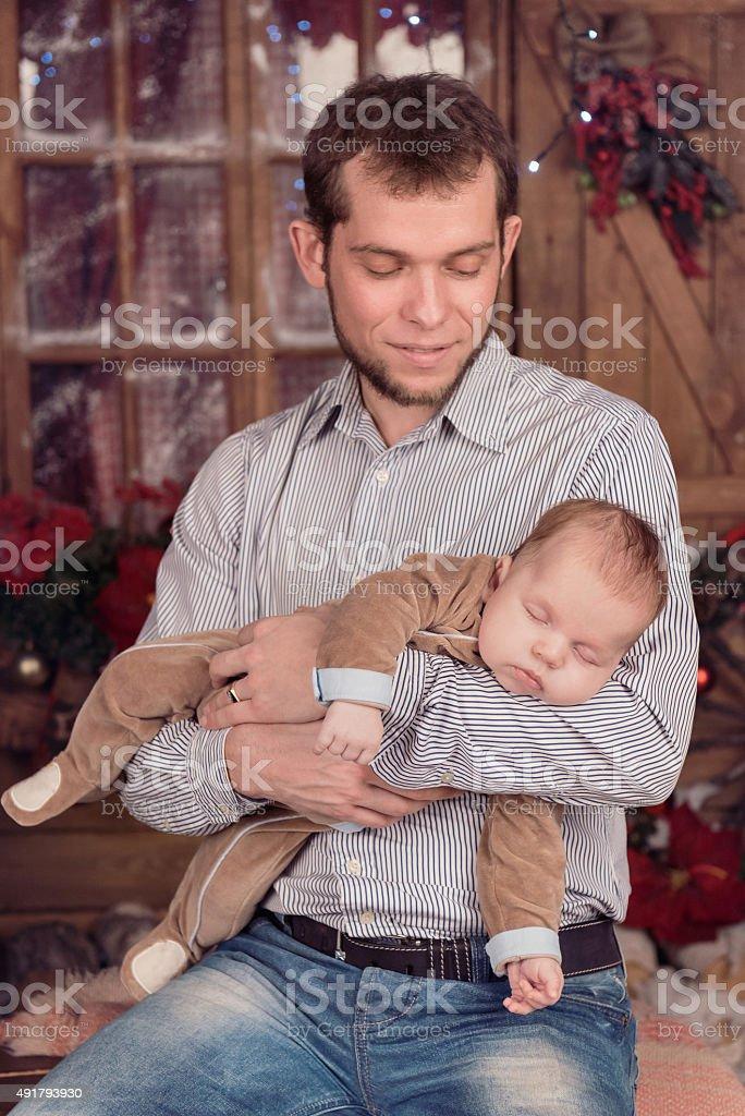 Father holding sleeping baby boy on Christmas eve stock photo
