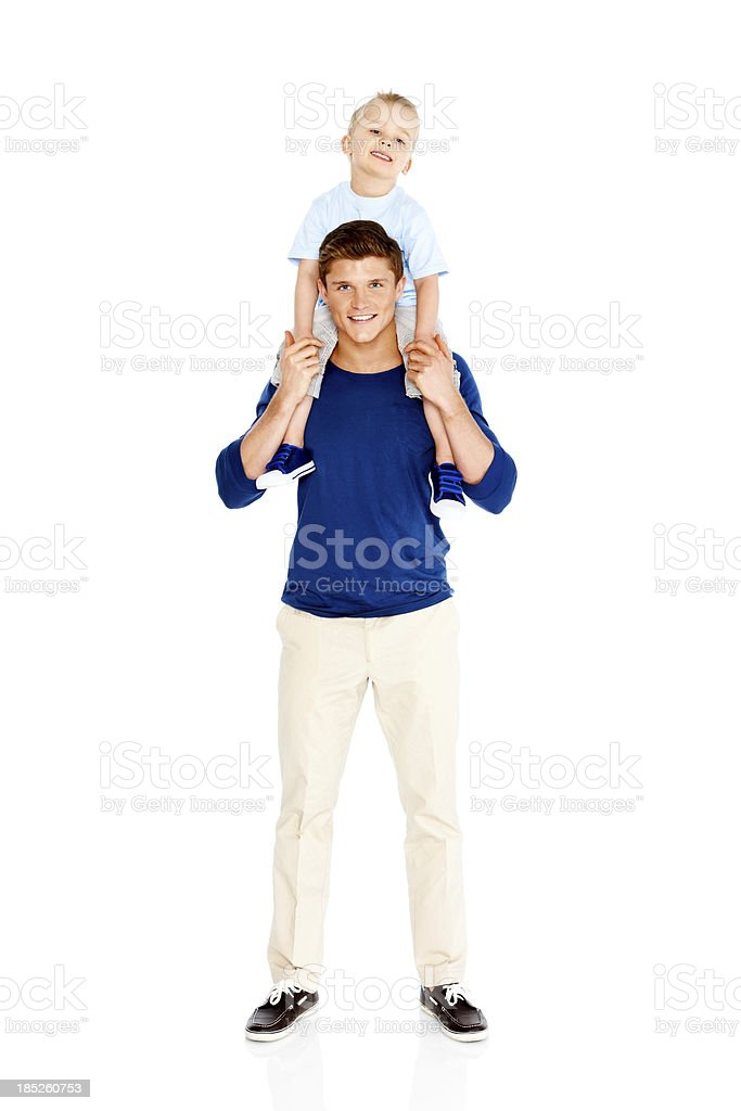 Father holding son on shoulders against white background stock photo