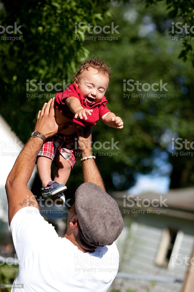 Father Holding Up His Little Son in Outdoor Setting royalty-free stock photo