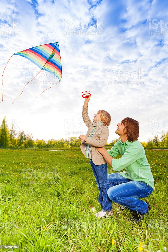 Father holds kid while watching flying kite stock photo