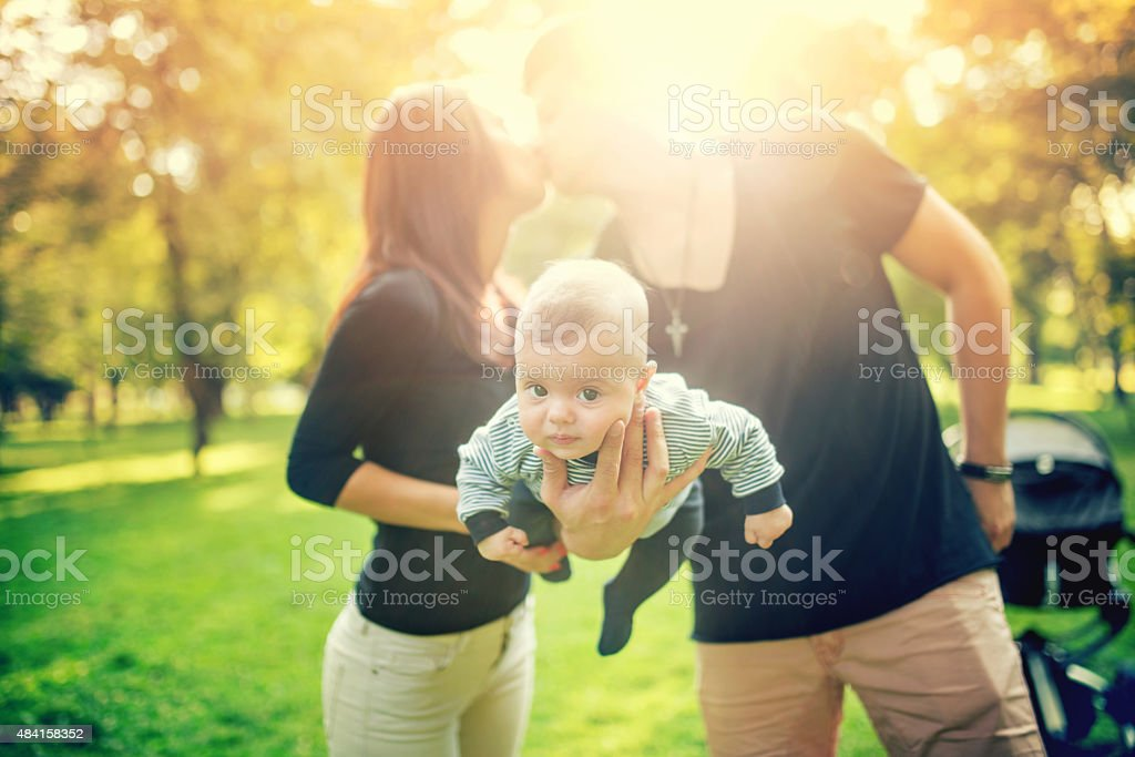father holds newborn baby on arm while kissing the mother stock photo