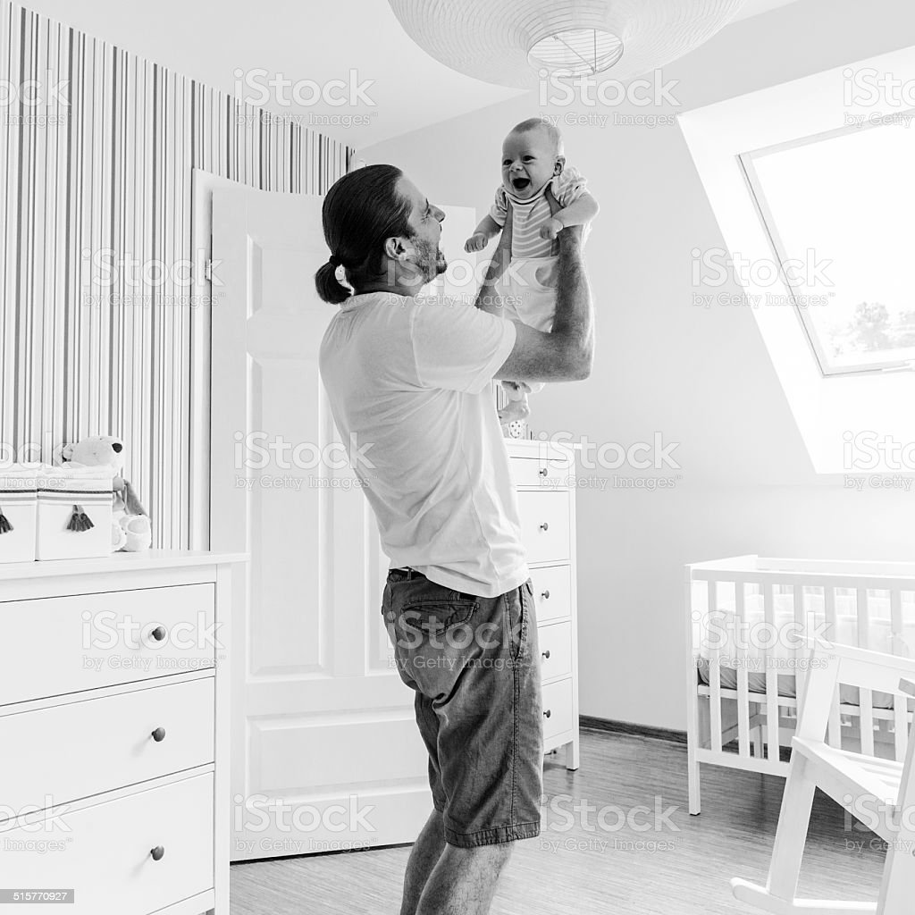 Father holds on hands son, smiling to him and playing stock photo