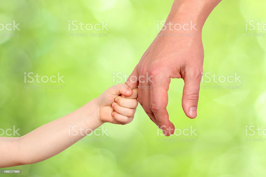 Father holds the hand of a small child stock photo