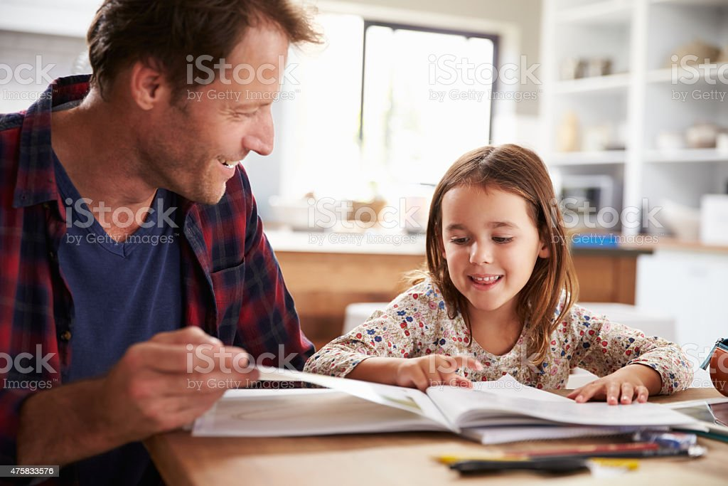 Father home schooling his young daughter stock photo