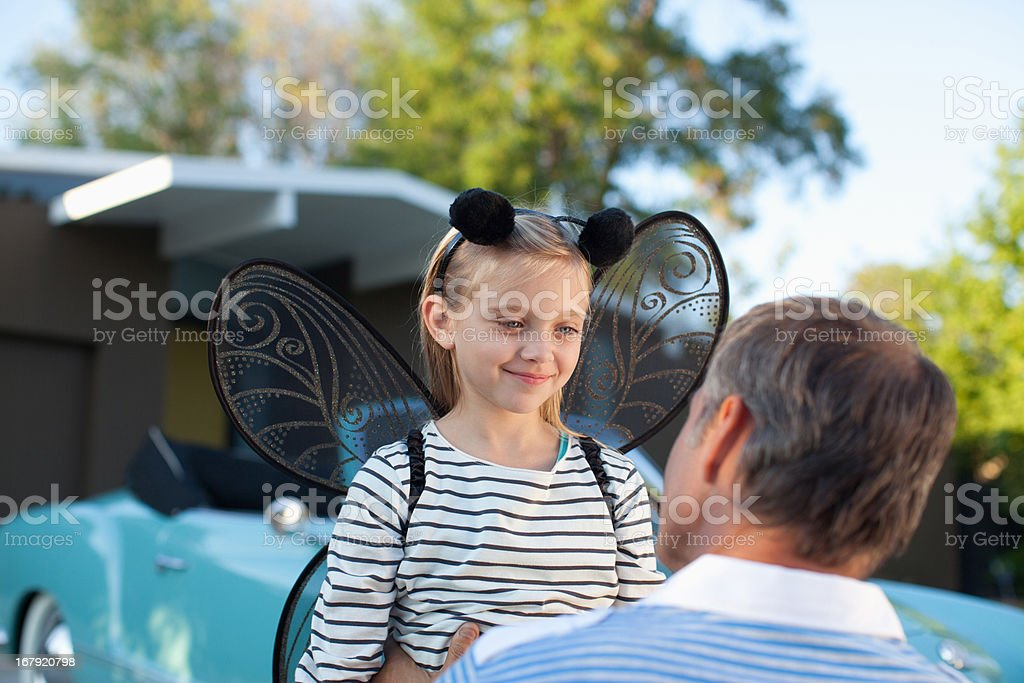 Father hugging daughter in fairy wings stock photo