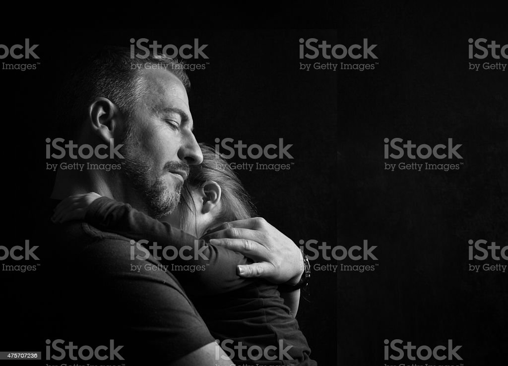 Father Hugging Daughter Tenderly stock photo