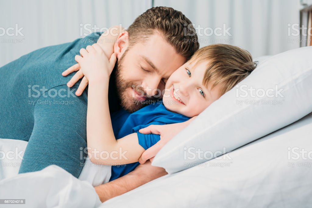 Father hugging smiling little son lying in hospital bed, dad and son in hospital stock photo