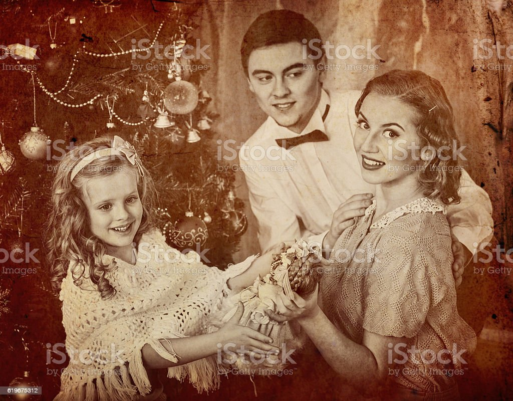 Father hugs his wife with daughter and dressing Christmas tree. stock photo