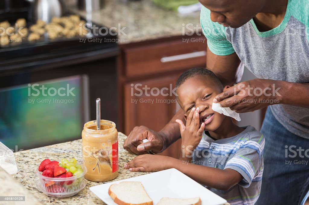 Father in kitchen taking care of little boy, wiping nose stock photo