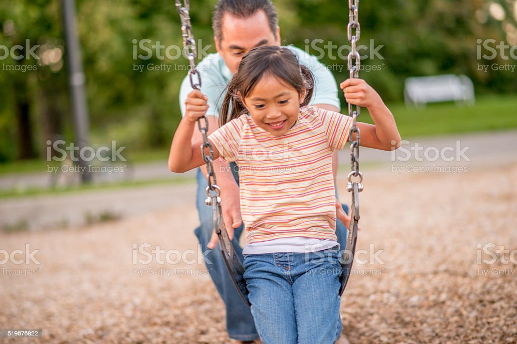 A father is pushing her daughter on the swing. They stock photo