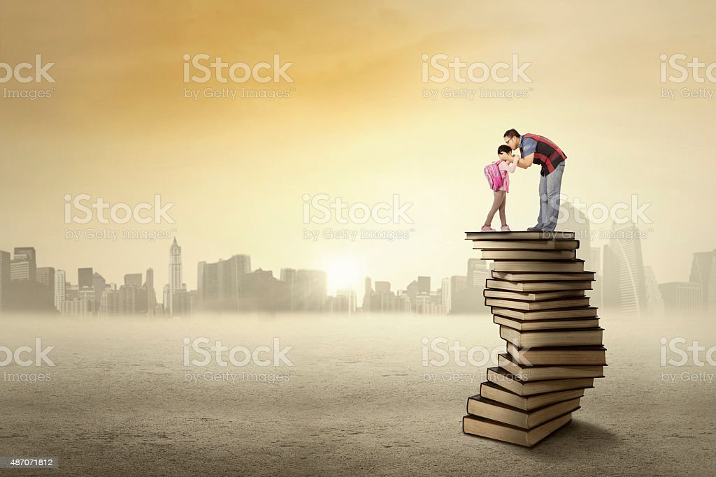 Father kiss his kid above a pile of books stock photo