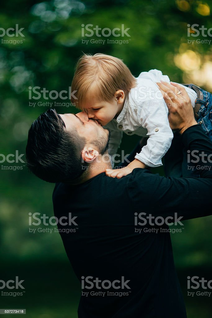 Father kiss his son in arms stock photo