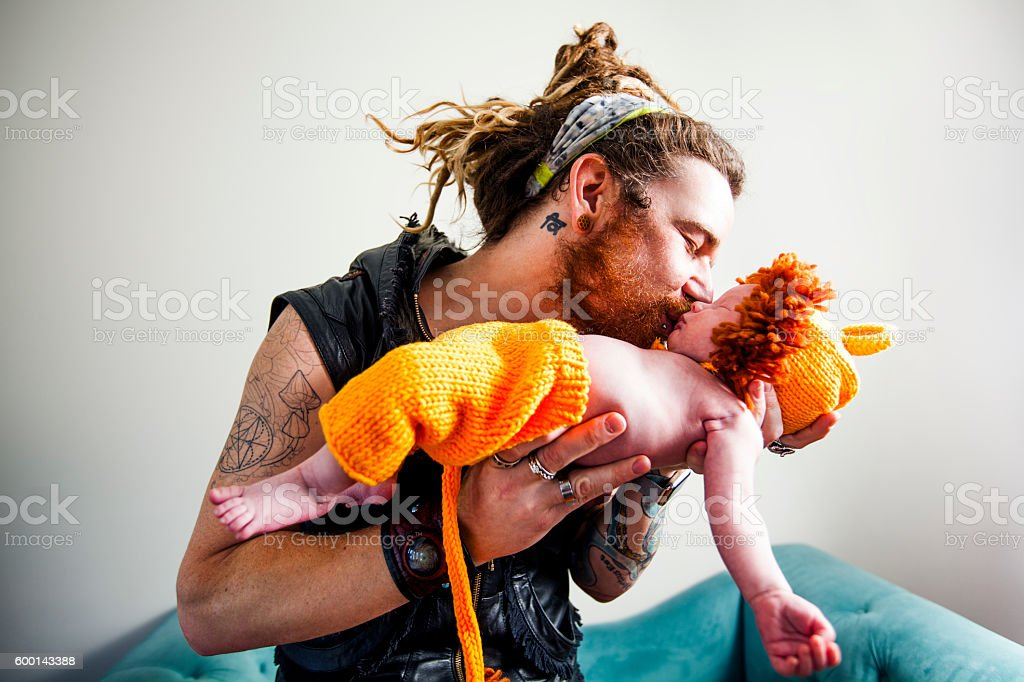 Father Kissing His Baby Boy Wearing Lion Cub Costume stock photo
