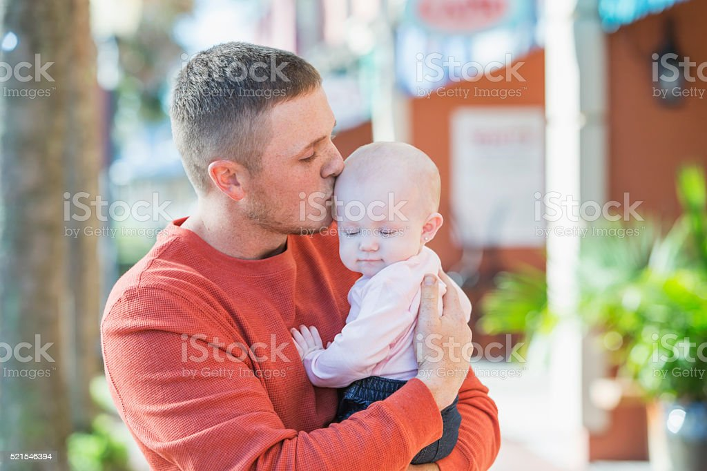 Father kissing his baby girl on her head stock photo