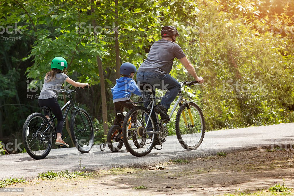 Father leading his kids on bike ride in park stock photo