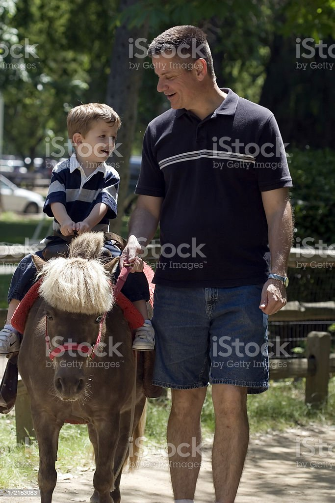 Father leads son on brown pony royalty-free stock photo