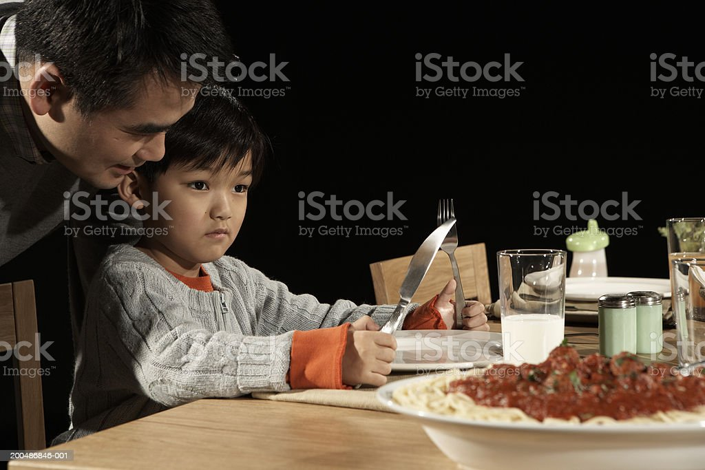 Father leaning over son's (3-5) shoulder at dining table royalty-free stock photo