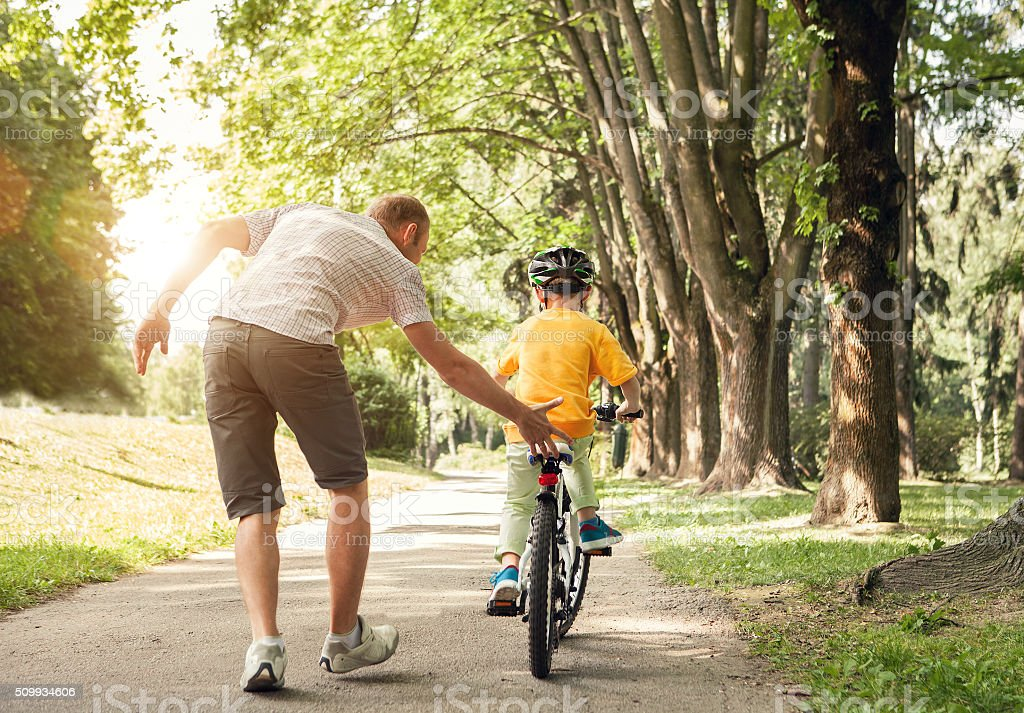 Father learn his little son to ride a bicycle royalty-free stock photo