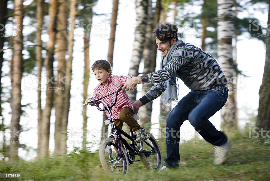 father learning his son to ride on bicycle stock photo