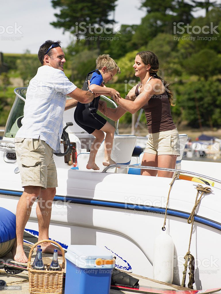 Father lifting boy onto boat stock photo