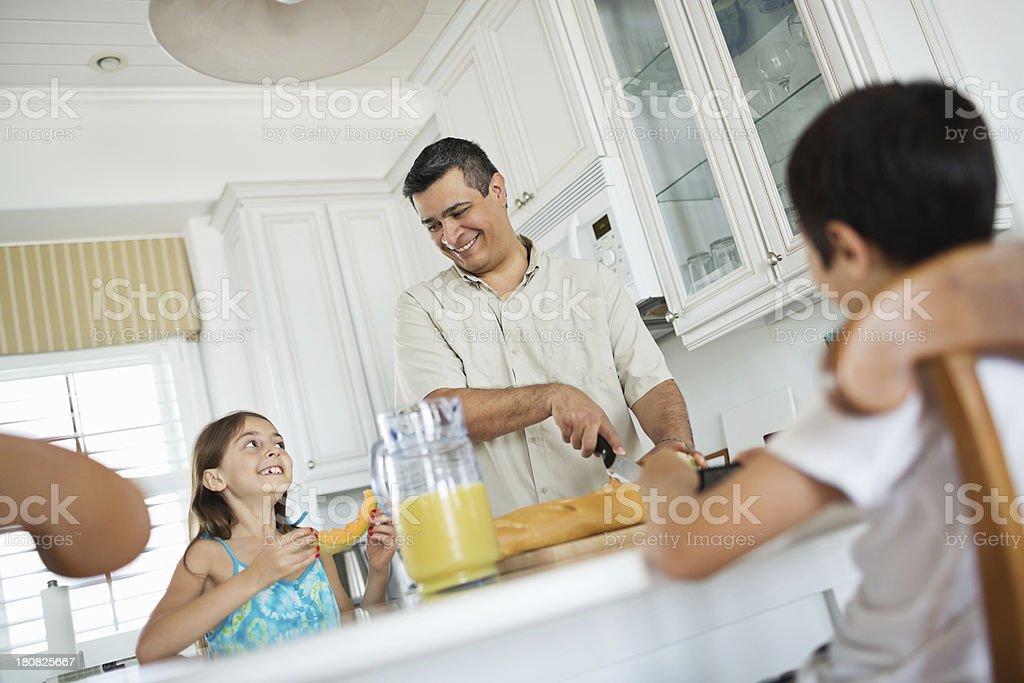 Father Looking At Daughter While Preparing Breakfast In Kitchen royalty-free stock photo