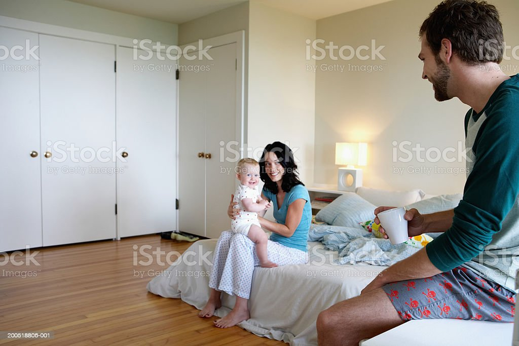 Father looking at mother with baby girl (9-12 months) in bedroom royalty-free stock photo