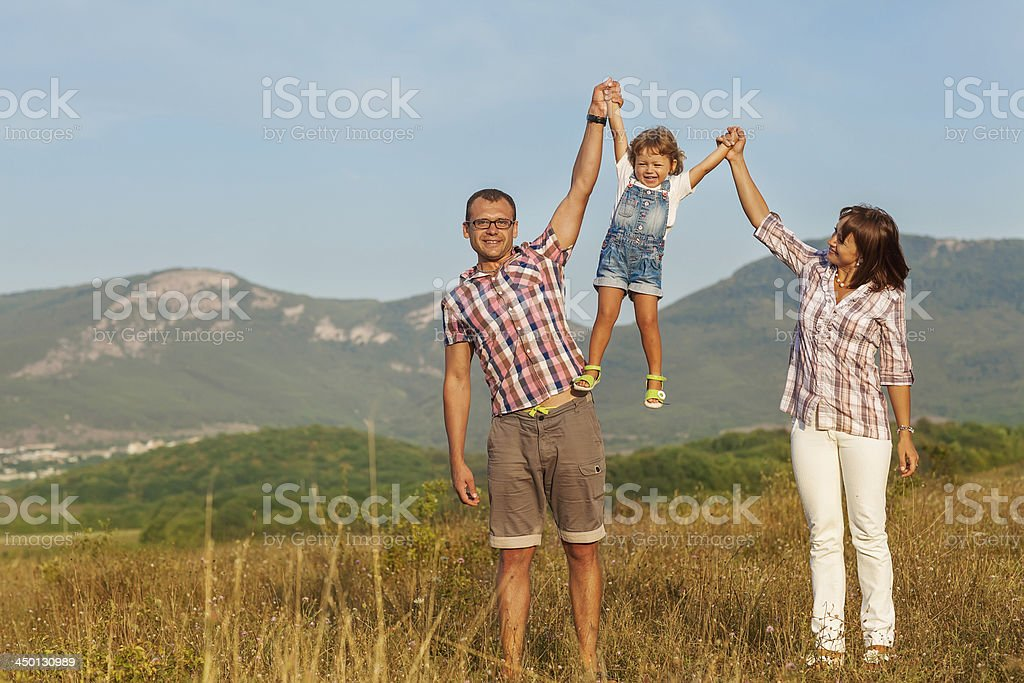 Father mother and daughter walking on the field royalty-free stock photo