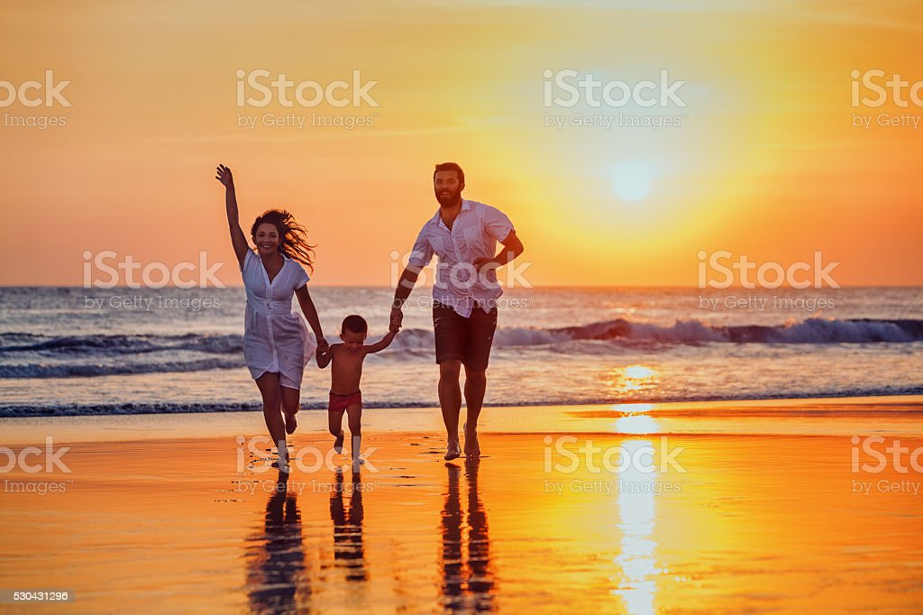 Happy family - father, mother, baby son hold hands and run with fun...