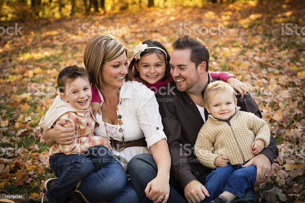 Father, Mother, Daughter, and Sons Sitting Outside on Fall Day royalty-free stock photo