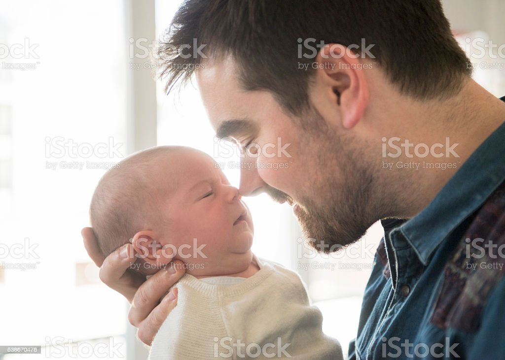 Father nuzzling newborn baby son stock photo