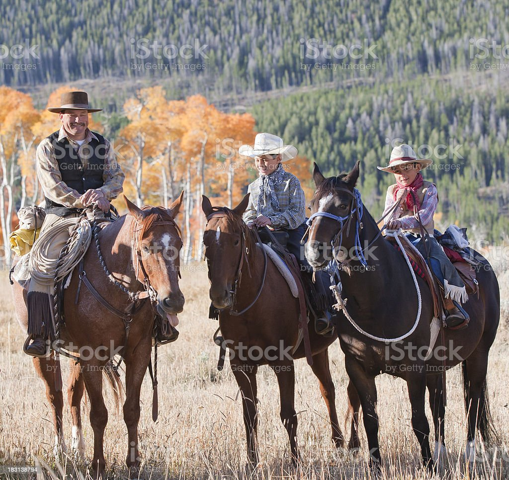Father on horse with two young sons learning to ride royalty-free stock photo