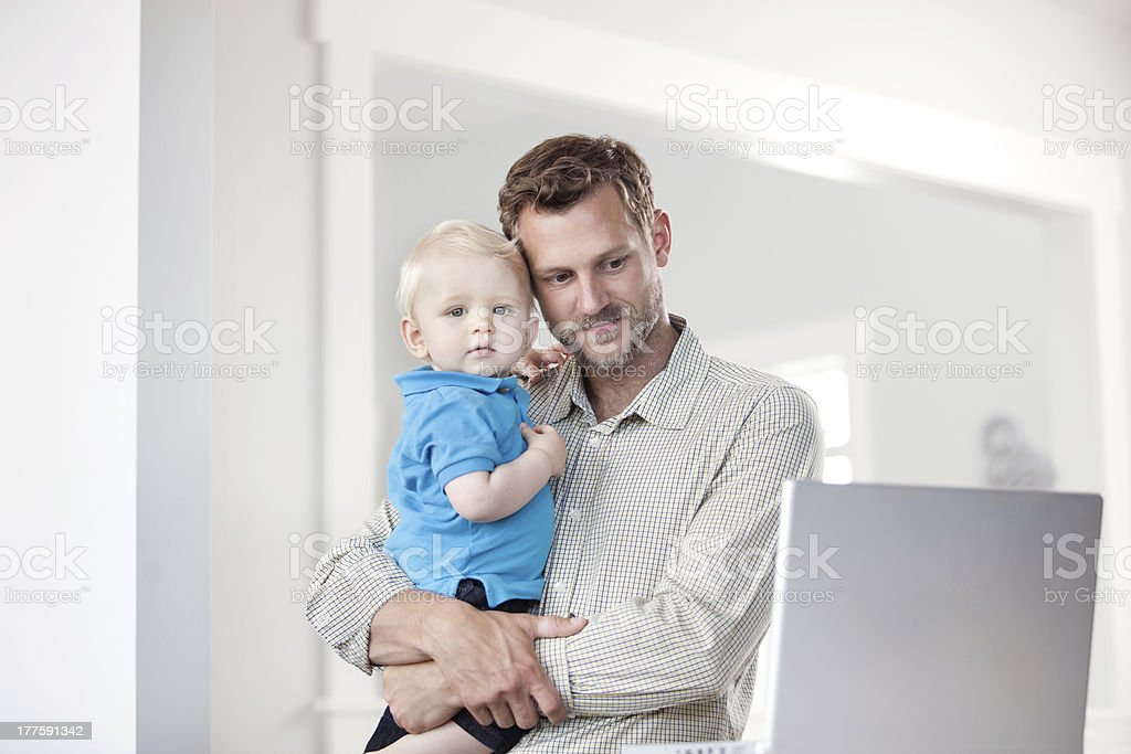 Father on laptop with his son royalty-free stock photo