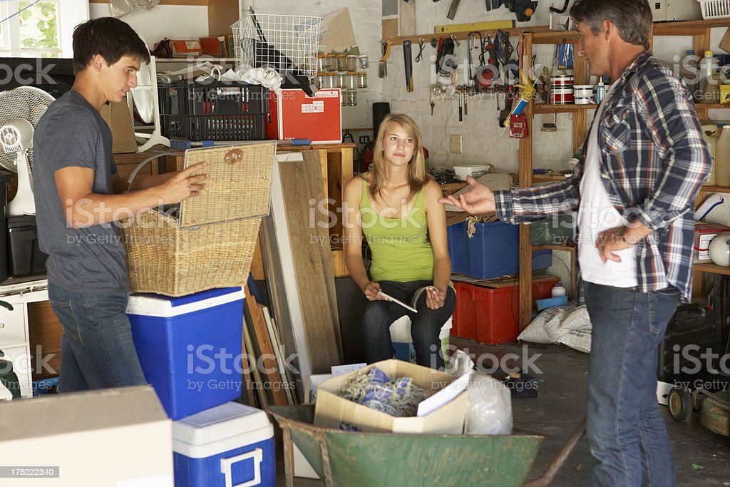 Father Organising Teenagers Clearing Garage stock photo