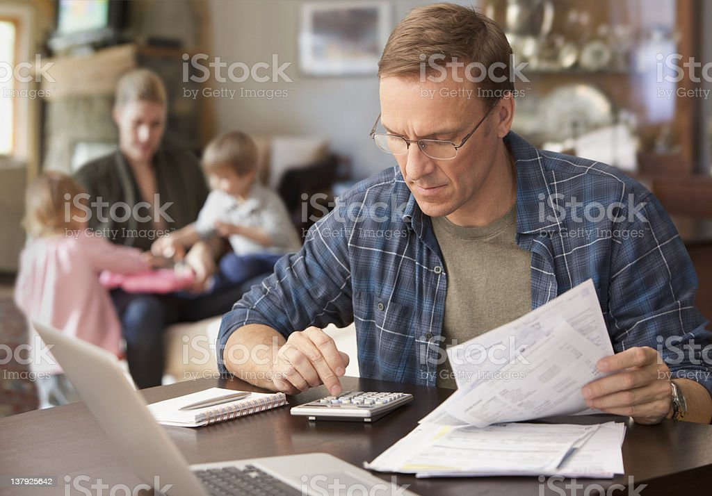 Father paying bills with family behind him stock photo