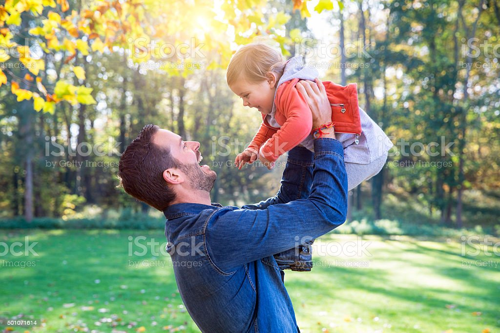 Father picking up his daughter stock photo