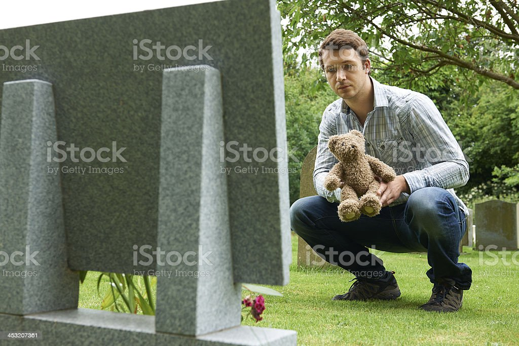 Father Placing Teddy Bear On Child's Grave In Cemetery royalty-free stock photo