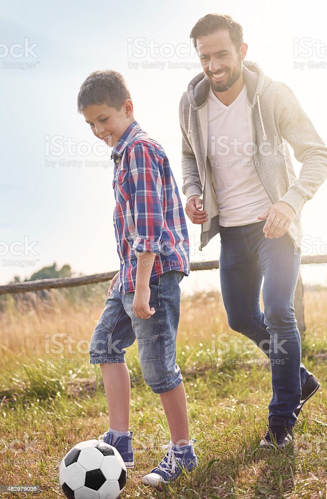 Father playing football with his son stock photo